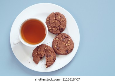 Plate with cup of tea and chocolate cookies with nuts is located on an blue table, top view