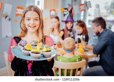 Plate with cupcakes. Beaming dark-eyed schoolgirl wearing Halloween dress holding plate with yummy bright cupcakes