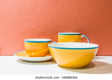 Plate  and cups with orange wall and white floor, Thailand.