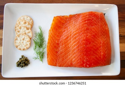 Plate of Cured salmon, grav lax, accompanied with crackers, capers and dill, top-down composition
