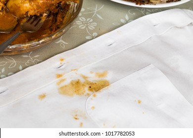 Plate of curry chicken and white shirt with curry stain accicently spilled.