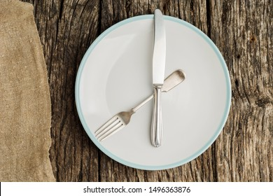 Plate and cutlery on rustic wooden table with canvas. Flat lay.