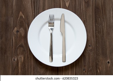 Plate and cutlery on wooden background in finished form
