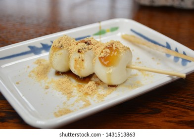 A plate with dango stick - a traditional Japanese sweet made out of rice powder. Topped with brown sugar syrup and kinako powder.