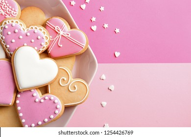 Plate with decorated heart shaped cookies and candy confetti on color background, top view. Space for text