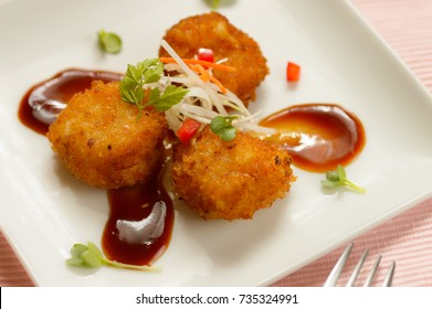 a plate of deep fried breaded scallops