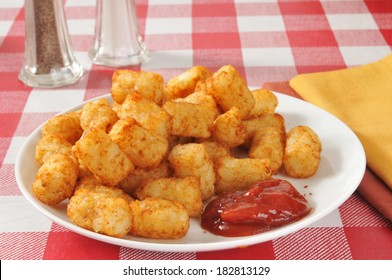 A plate of deep fried tater tots with catsup