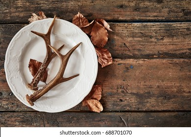 Plate with deer antlers and dry leaves on wooden table