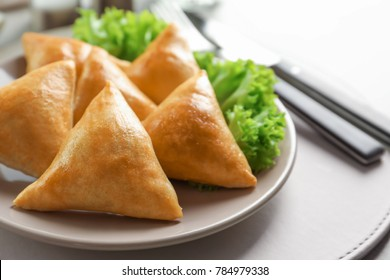 Plate with delicious baked samosas on table, closeup