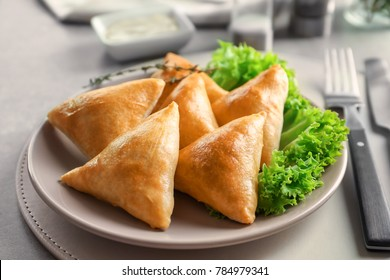 Plate with delicious baked samosas on table
