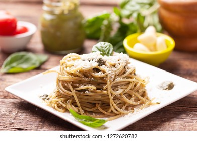 Plate with delicious basil pesto pasta on  a rustic table