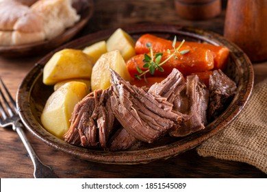 A plate of delicious beef pot roast with potatoes and carrots with thyme garnish.