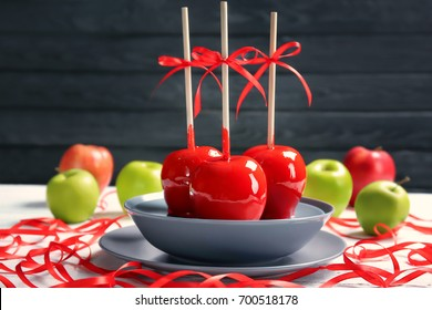 Plate with delicious candy apples on table