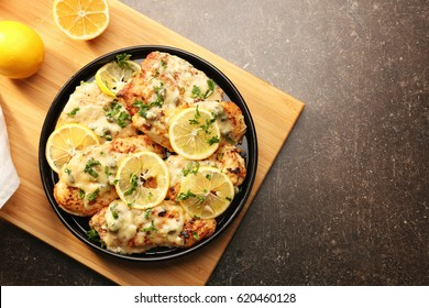 Plate with delicious chicken piccata on wooden board