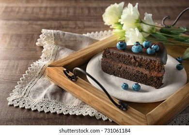 Plate with delicious chocolate cake on wooden tray