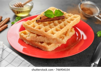 Plate with delicious cinnamon waffles on table