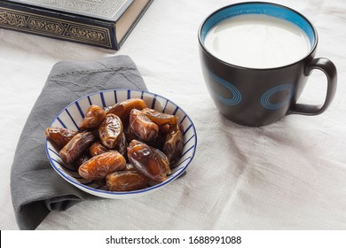 Plate of delicious dates with a cup of laban or fermented milk on a white linens table background with empty copy space and napkins and a part of holy Quran. Highly nutritious food for Ramadan stills.