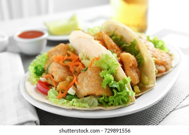 Plate with delicious fish tacos on table, closeup