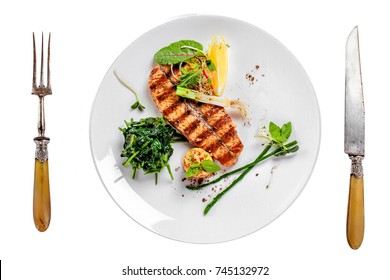 Plate with delicious grilled salmon fish steak and salad isolated on white background. Healthy food made of fish and vegetables. Top view.