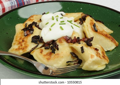 Plate of delicious homemade perogies and sour cream.