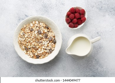A plate of delicious muesli, a jug of milk and raspberries on the table, top view. Muesli consist of a blend of multigrain flakes with dried fruit, nuts and sunflower seeds