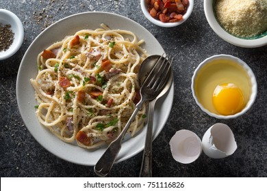 A plate of delicious pasta carbonara with fettuccine, bacon, parsley, parmesan cheese and egg.