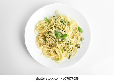 Plate with delicious pasta on white background