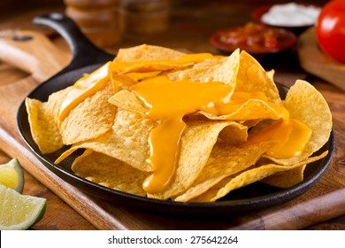 A plate of delicious plain nacho tortilla corn chips with cheese sauce.