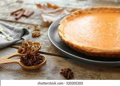 Plate with delicious pumpkin cake and ingredients in wooden spoons, closeup