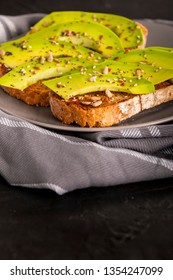 Plate of delicious sandwiches with slices of fresh avocado and spices placed on towel in kitchen