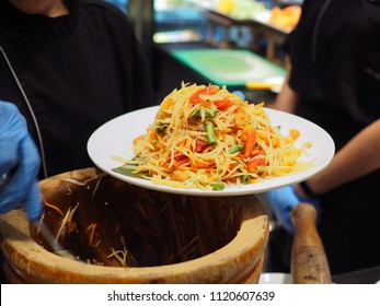 A plate of delicious and savory Thai spicy papaya salad (Som Tum) with fresh papaya, dried shrimp, tomato, long bean, carrot, chili, garlic and peanut on marble table background with selective focus.