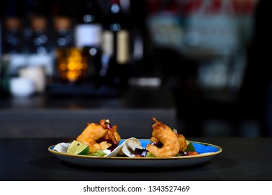 Plate with delicious shrimp appetizers on dark background.
