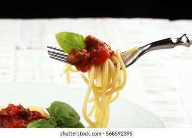 Plate of delicious spaghetti Bolognaise or Bolognese with savory minced beef and tomato sauce garnished with parmesan cheese and basil
