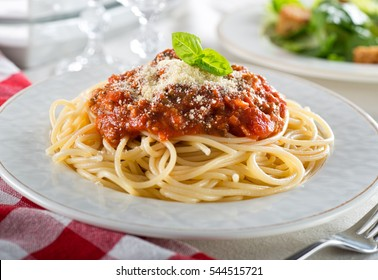 A plate of delicious spaghetti bolognese with meat sauce and fresh basil.