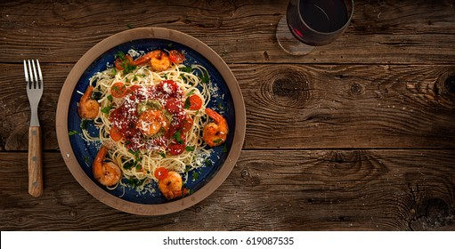 Plate of delicious spaghetti with shrimps and parmesan cheese, overhead view