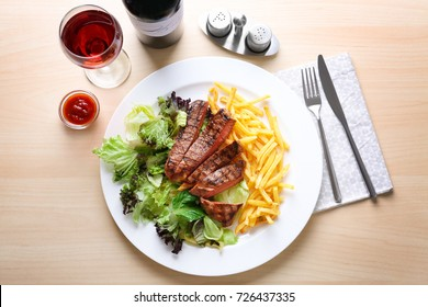 Plate with delicious steak and garnish on table in cafe