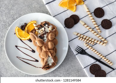 Plate with delicious sweet bubble waffle on grey table