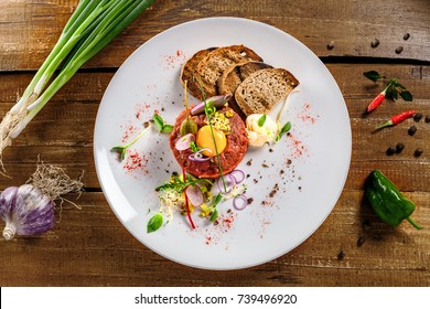 Plate with delicious tartare, toasted bread and salad on a wooden table. Healthy gourmet French food made of raw meat. Top view.