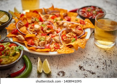 A plate of delicious tortilla nachos with melted cheese sauce, grilled chicken, jalapeno peppers, red onion, tomato, guacamole dip and spicy salsa. With cold sparkling beer.