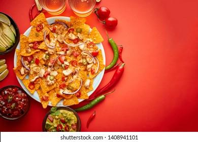 Ein Teller mit köstlichen Tortilla nachos mit geschmolzener Käsesauce, gegrilltem Huhn, Paprika aus Jalapeno, roter Zwiebel, Tomate, Guacamoldip und würzigen Salsa. Mit kaltem Schaumbier. Auf rotem Hintergrund platziert