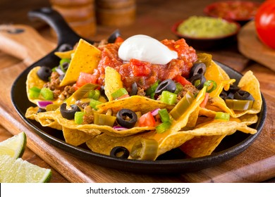 A plate of delicious tortilla nachos with melted cheese sauce, ground beef, jalapeno peppers, red onion, green onions, tomato, black olives, salsa, and sour cream with guacamole dip.