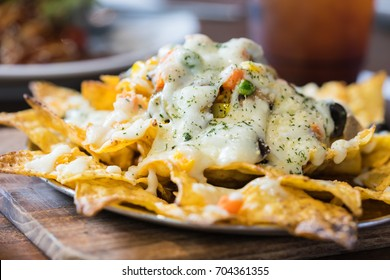 A plate of delicious tortilla nachos with melted cheese sauce and dressing. Food background.