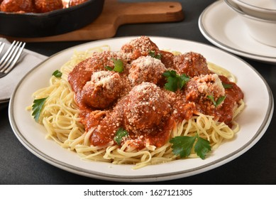 A plate of delicsious spaghetti and meatballs with a marinara sauce