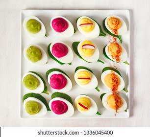 A plate of deviled eggs on dark grey stone background, top view