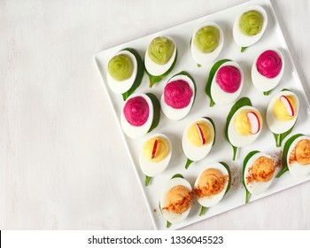 A plate of deviled eggs on dark grey stone background, top view, copy space