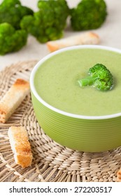 Plate of dieting healthy broccoli cream soup with croutons on vintage background
