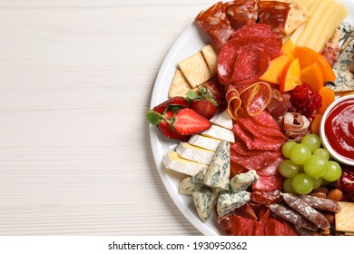 Plate of different appetizers with dip sauce on white wooden table, top view. Space for text