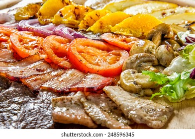 Plate of different kinds grilled meat with fruits and vegetables