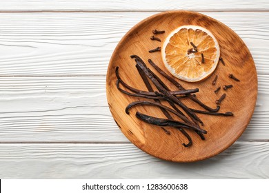 Plate with dry orange slice and aromatic vanilla sticks on white wooden background