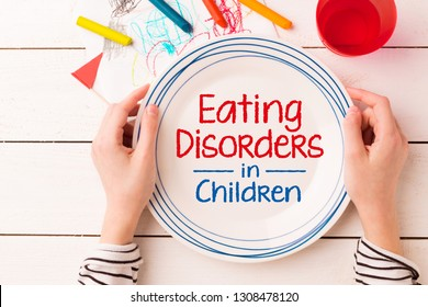 Plate with 'Eating Disorders in Children' sign in kid's hands. Anorexia and bulimia problem - concept captured from above (top view, flat lay). Crayons and child's drawing around.
